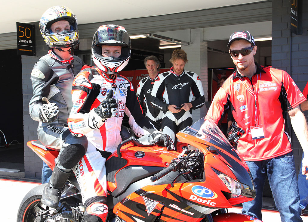 Andrew Downie on the back of Jamie Stauffer at Sydney Motorsport Park with Team Honda