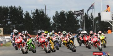 The Swann Australasian Superbike field streams into turn one at Wakefield Park