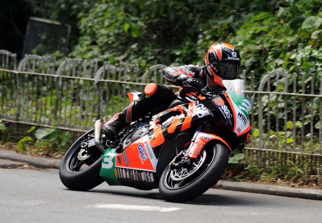 Ryan Farquhar on the KMR Kawasaki lightweight bike at Braddan bridge during the Bike Nation Lightweight race at the 2014 Isle of Man TT