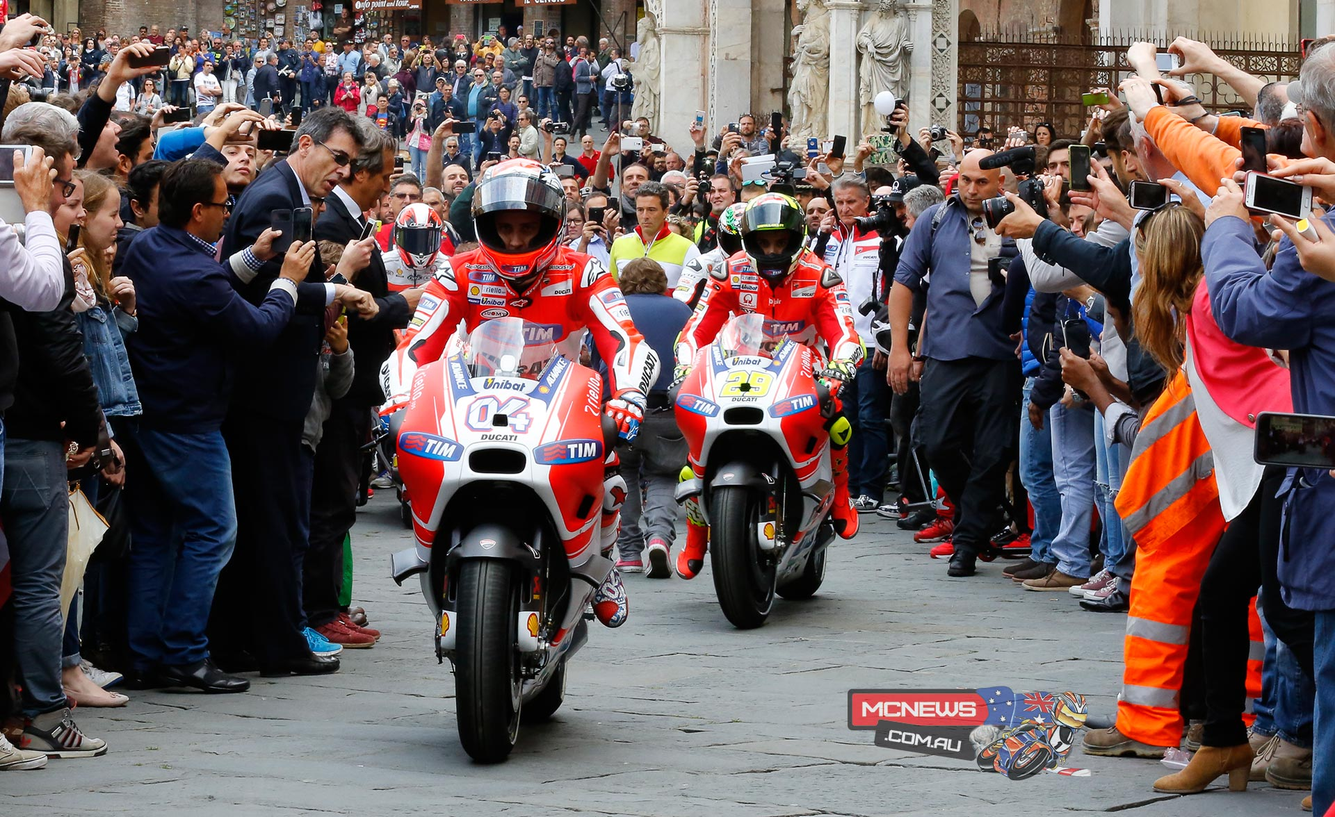 The Ducatis ride among the Siena crowd.