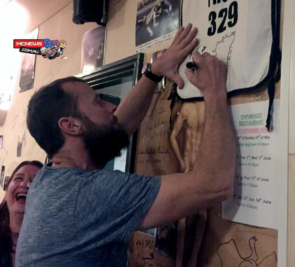 Bruce Anstey celebrating at a pub on Sunday night and signing a shirt for the host