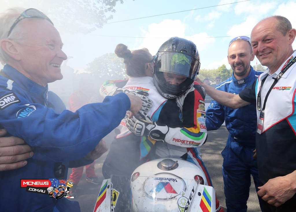 Bruce Anstey congratulated by his partner, team manager Clive Padgett and team members
