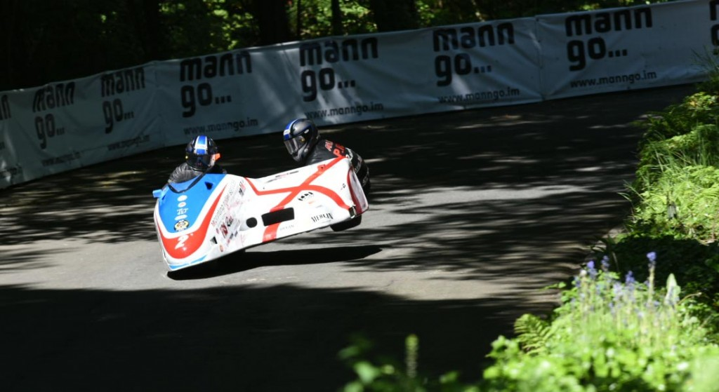 IOM TT 2015 - Sidecar Race Two - Conrad Harrison and Mike Aylott get the chair wheel in the air at Governors Bridge. Credit Dave Kneale