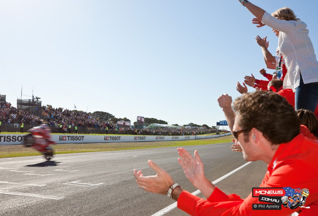 Casey Stoner crosses the finish line to win the Australian GP as team & family cheer him on. Phillip Island 2008. BY Phil Aynsley