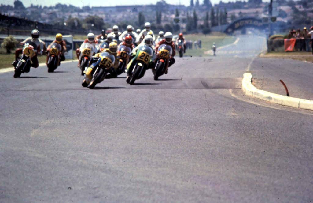 A full field at Sandown Raceway jostle for position in front of cheering crowds.