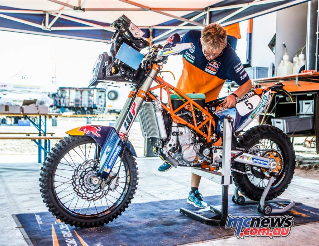Toby Price's KTM 450 Rally gets worked on by a mechanic between stages