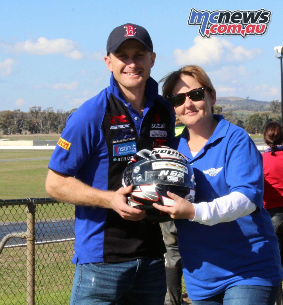 Loza Weaves hands over the helmet to winner