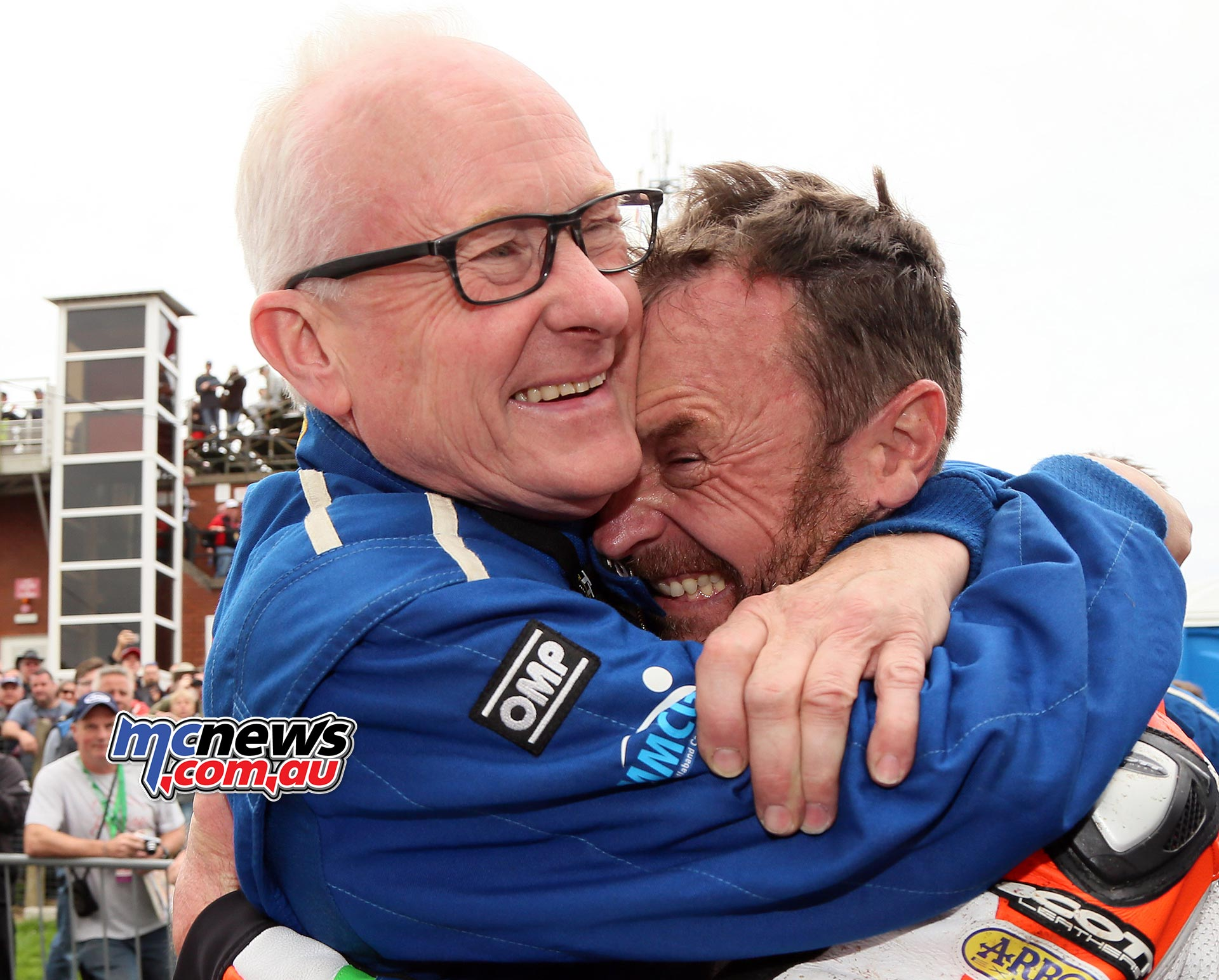 Clive Padgett hugs Bruce Anstey after his record-setting win in the Dunlop Lightweight Classic TT Race. Photo Stephen Davison / Pacemaker Press Intl