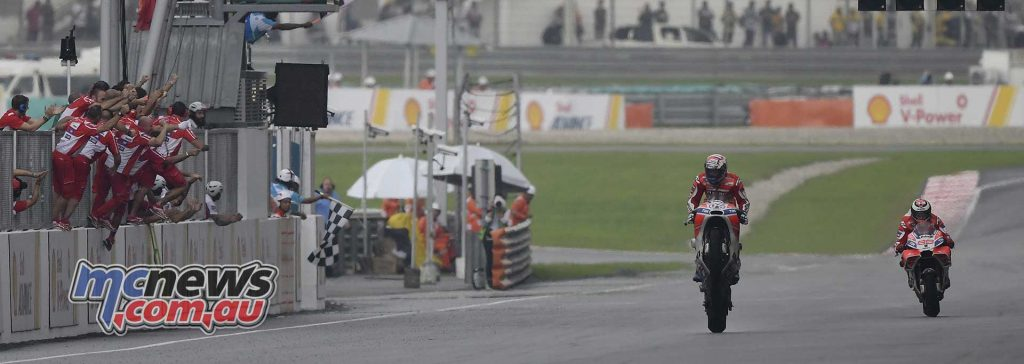 Andrea Dovizioso celebrated a brilliant tactical victory with a fine stand-up mono across the line at Sepang