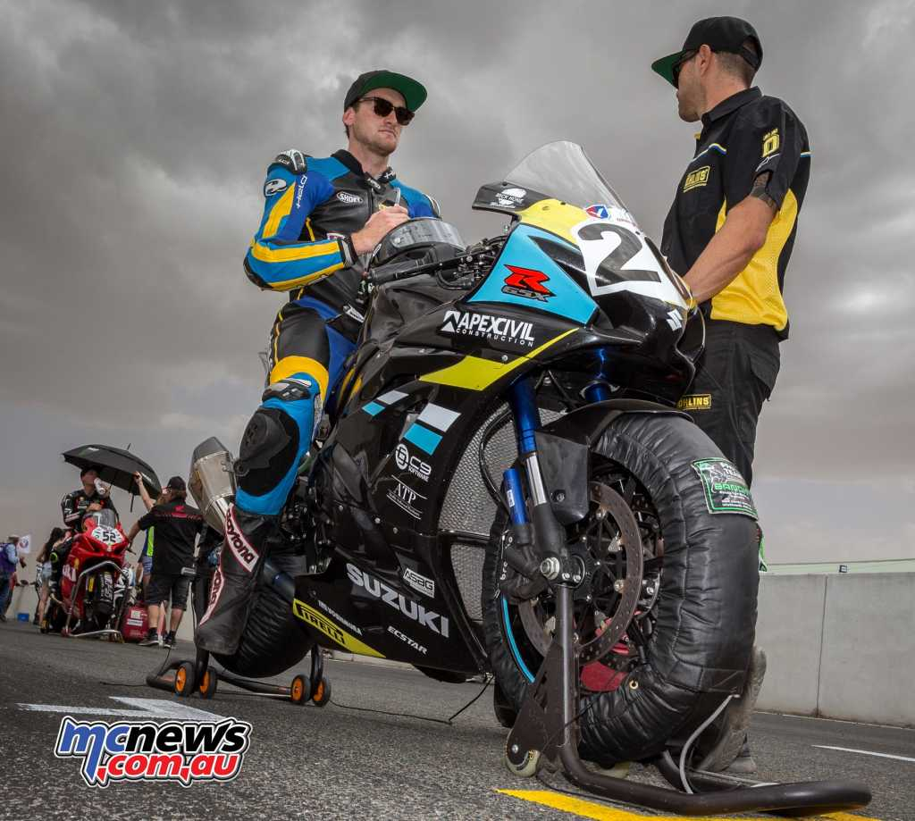 Alex Phillis on the grid with the clouds and sandstorm in the background - Image by TBG Sport