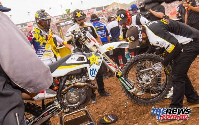 Jason Anderson looks on while his mechanics change the front wheel